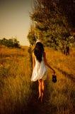 Het blootvoetse meisje in witte kleding is op het gebied Royalty-vrije Stock Afbeeldingen