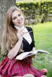 Het boek/de student die van de meisjeslezing een boek in park lezen/ Royalty-vrije Stock Afbeeldingen