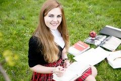 Het boek/de student die van de meisjeslezing een boek in park lezen/ Stock Afbeeldingen