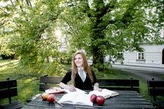 Het boek/de student die van de meisjeslezing een boek in park lezen/ Stock Fotografie