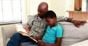Het boek en de zoon die van de vaderlezing digitale tablet in woonkamer 4k gebruiken stock video