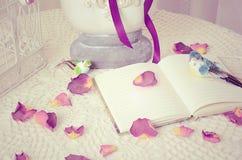 Het boek op een lijst met roze bloemblaadjes Stock Afbeeldingen
