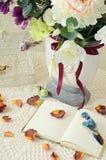 Het boek op een lijst met roze bloemblaadjes Stock Foto's