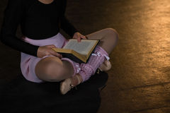 Het boek van de ballerinalezing terwijl het zitten op het stadium in theater royalty-vrije stock foto
