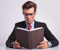 Het boek van de bedrijfsmensenlezing bij zijn bureau Royalty-vrije Stock Fotografie