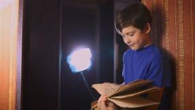 Het boek van de de jongenslezing van het tieneronderwijs is muur binnen stock videobeelden