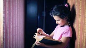 Het boek van de het kindlezing van het tienermeisje terwijl status stock footage