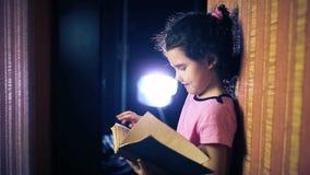 Het boek van de het kindlezing van het tienermeisje terwijl status stock video