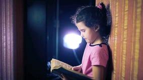 Het boek van de het kindlezing van het tienermeisje terwijl status stock videobeelden