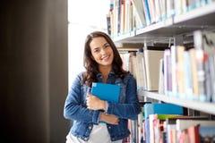 Het boek van de het meisjeslezing van de middelbare schoolstudent bij bibliotheek Stock Afbeelding