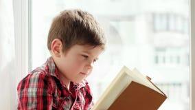 Het boek van de jong geitjeholding, slimme jongen het wegknippen pagina's van schoolbook, het portret van de kindclose-up, het bo stock footage