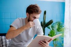 Het boek van de jonge mensenlezing en het drinken koffie op bank Stock Afbeeldingen