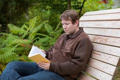 Het boek van de jonge mensenlezing op bank in de herfstbos Stock Fotografie