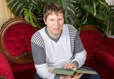 Het boek van de jonge mensenlezing op rode laag binnen Stock Fotografie