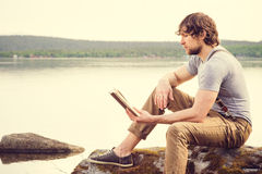 Het boek van de jonge Mensenlezing openlucht met Skandinavisch meer op achtergrond stock afbeelding