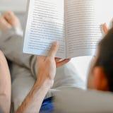 Het boek van de jonge mensenlezing terwijl het liggen op de laag Stock Afbeelding