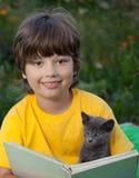 Het boek van de jongenslezing met katje in de werf, kind met huisdierenlezing Royalty-vrije Stock Afbeeldingen