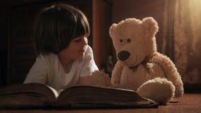 Het boek van de jongenslezing met zijn teddybeer royalty-vrije stock afbeelding