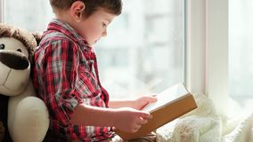 Het boek van de kindlezing, slim jong geitje die geruite rode overhemdszitting op venster en holding dragen boekt stock footage