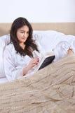 Het boek van de lezing op bed Stock Foto's