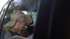 Het Boek van de meisjeslezing binnen Auto in achterbank stock footage