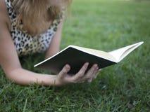 Het boek van de meisjeslezing en het liggen op gras in de zomer Stock Afbeeldingen
