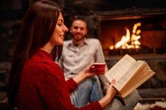 Het boek van de meisjeslezing met koffie voor open haard en het ontspannen Stock Foto