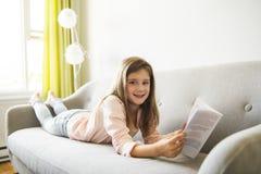 Het Boek van de meisjeslezing op Sofa In Living Room At-Huis stock afbeeldingen