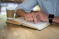 Het boek van de mensenlezing bij lijst in koffiewinkel Royalty-vrije Stock Afbeelding