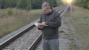 Het boek van de mensenlezing dichtbij spoorweg stock video