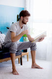 het boek van de mensenlezing en het drinken koffie op bank Stock Foto