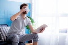 het boek van de mensenlezing en het drinken koffie op bank in het leven Royalty-vrije Stock Foto's
