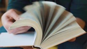 Het boek van de mensenlezing in koffie, het wegknippen pagina's stock videobeelden