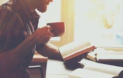 Het boek van de mensenlezing met koffie of thee Royalty-vrije Stock Afbeelding