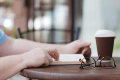 Het boek van de mensenlezing met koffie of thee Royalty-vrije Stock Foto