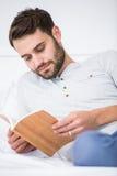 Het boek van de mensenlezing op bed thuis Royalty-vrije Stock Foto's