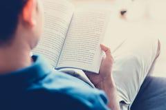 Het boek van de mensenlezing terwijl het zitten op de laag - uitstekende toon Royalty-vrije Stock Afbeelding