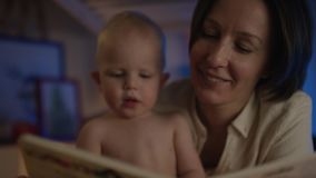 Het boek van de moederlezing aan haar leuke baby die op bed met differendbeelden liggen en geeft hem traktaties stock video
