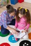 Het boek van de moederlezing met haar dochter thuis stock fotografie