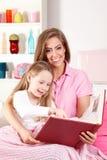 Het boek van de moederlezing met kind Stock Fotografie