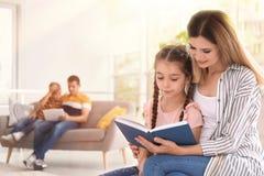 Het boek van de moederlezing met kind thuis stock afbeelding