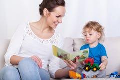 Het boek van de moederlezing van haar zoon Royalty-vrije Stock Foto