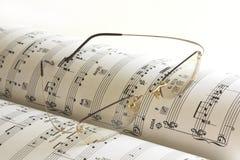 Het boek van de muziek en glazen Royalty-vrije Stock Foto's