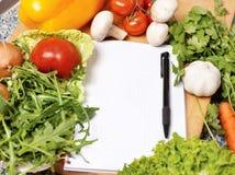 Het boek van de nota onder de groenten Stock Foto's