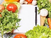 Het boek van de nota onder de groenten Stock Foto
