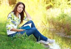 Het boek van de studentenlezing in de herfstpark. Stock Fotografie