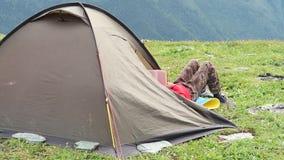Het boek van de toeristenlezing in tent bij het kamperen plaats in de bergen stock videobeelden