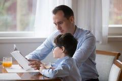 Het boek van de vaderlezing aan zoon hardop bij keuken thuis stock foto