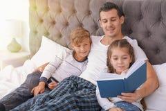 Het boek van de vaderlezing met kinderen in slaapkamer royalty-vrije stock foto