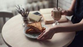Het boek van de vrouwenlezing en het drinken koffie bij koffie stock footage